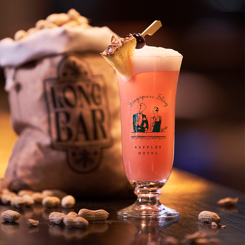 A singapore sling with a bag of peanut behind it at Long Bar