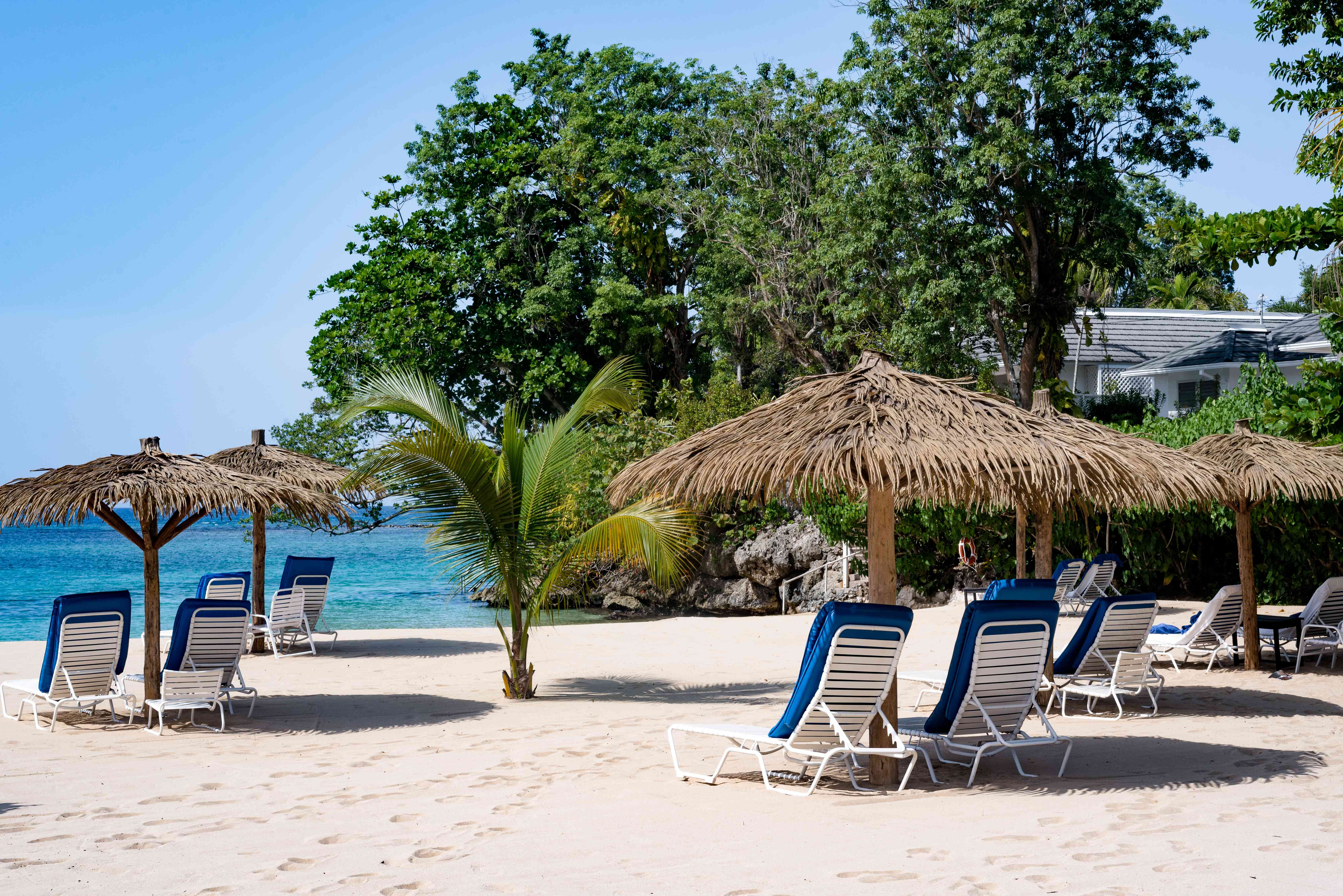 Lounge chairs under thatched umbrellas on a beach in Ocho Rios