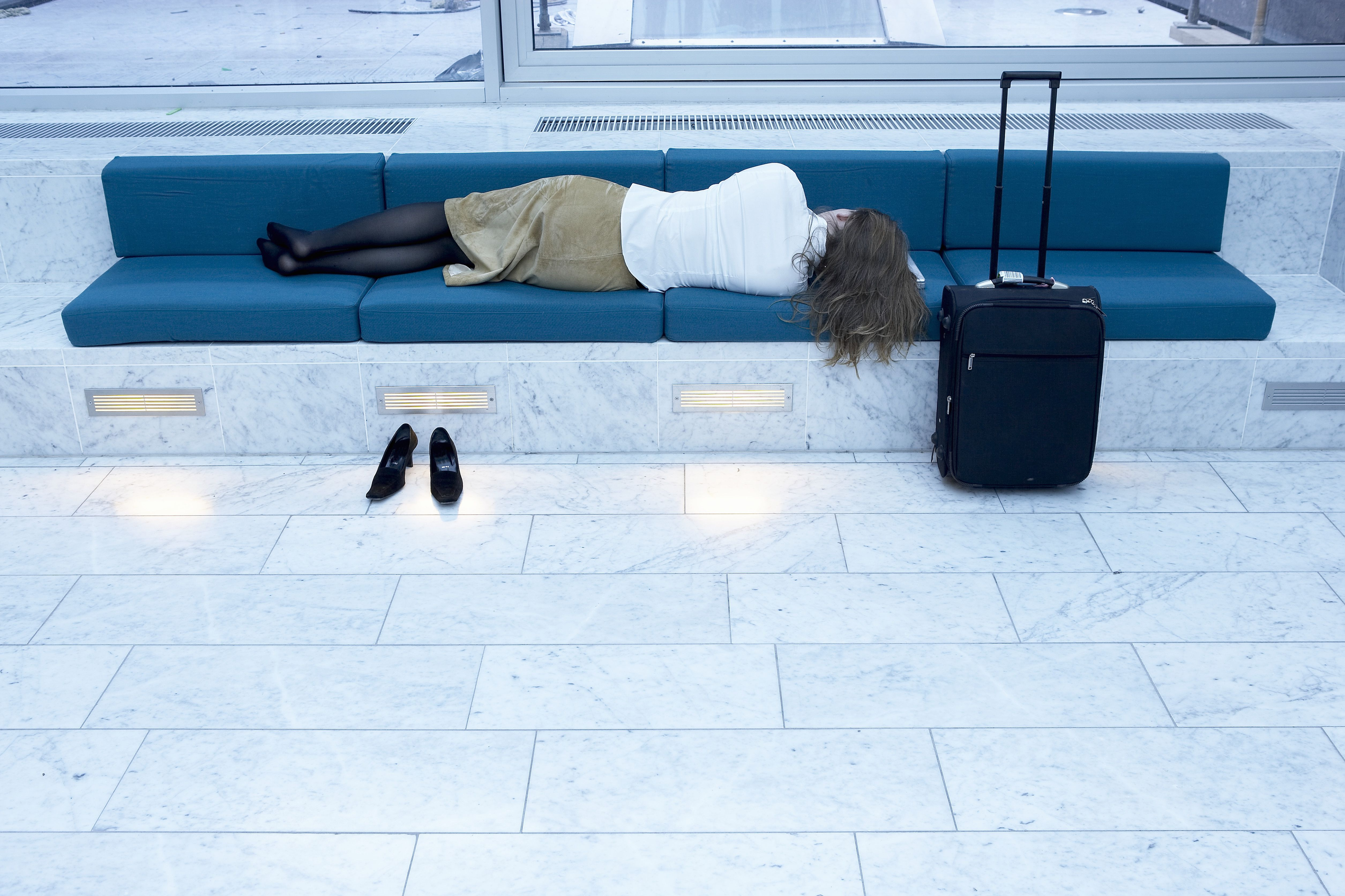 Woman sleeping on bench in airport