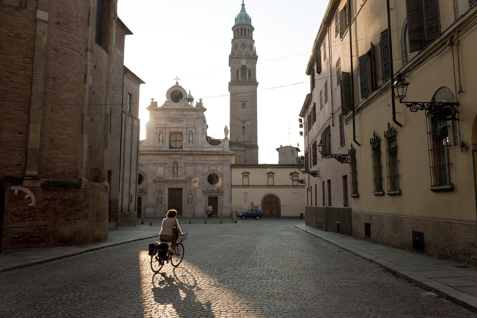 Person in Italy riding bike on cobblestone path towards tower
