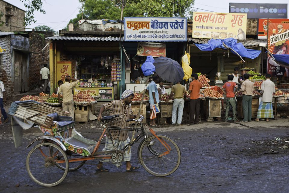 A man pushes his empty rickshaw down the road in a marketplace in Gorakhpur, India.