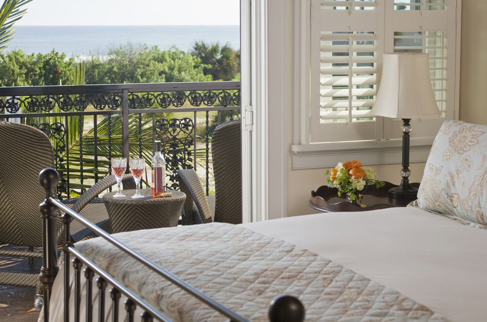 Wrought iron double bed with view through open door to balcony