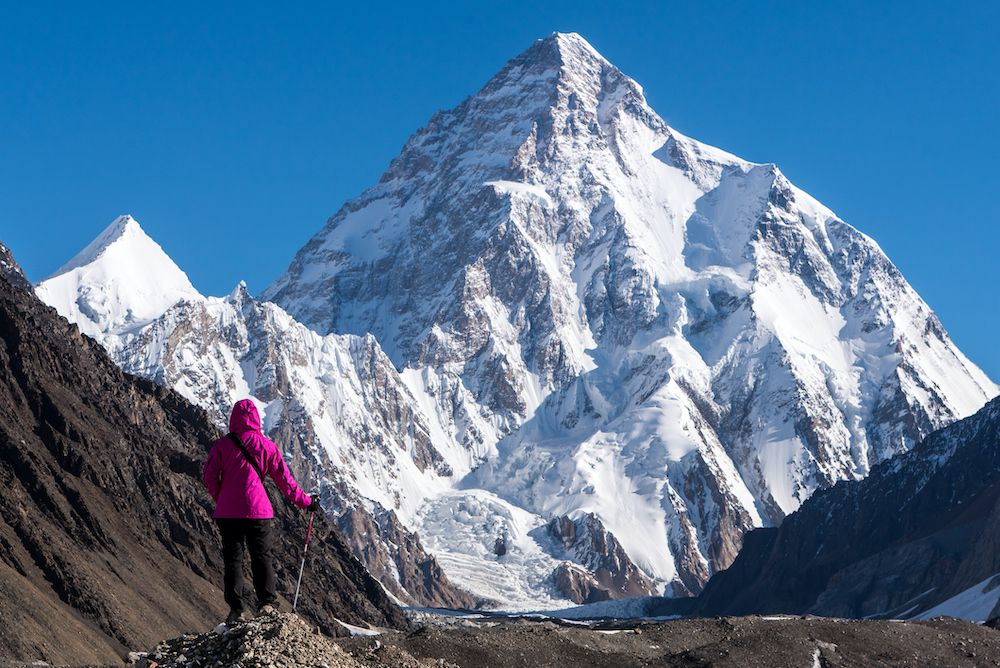 A hiker stands in front of a snowy peak in the Karakoram Range of Pakistan