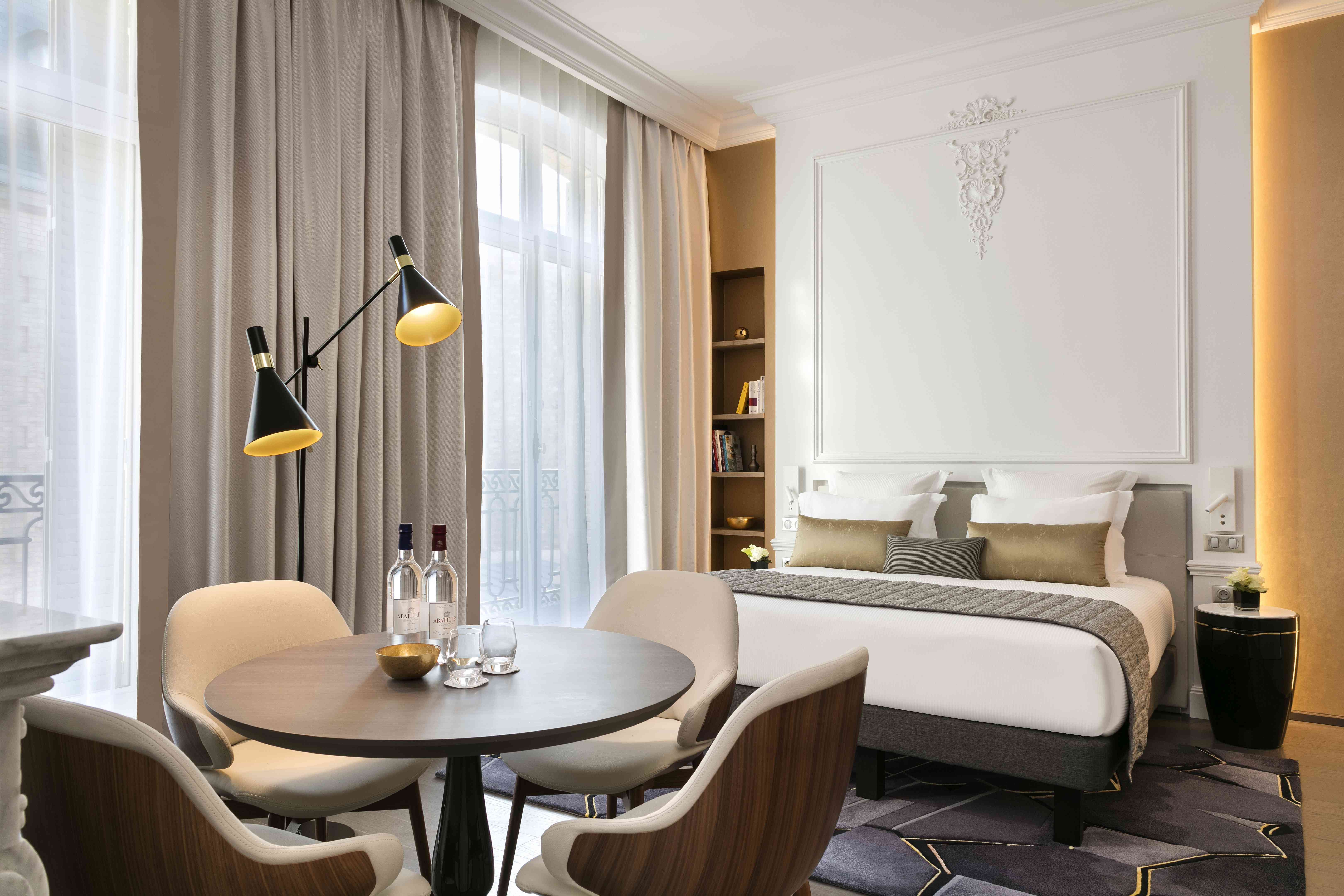 Deluxe Suite at Le Clef featuring a King Bed with a table and 4 chairs