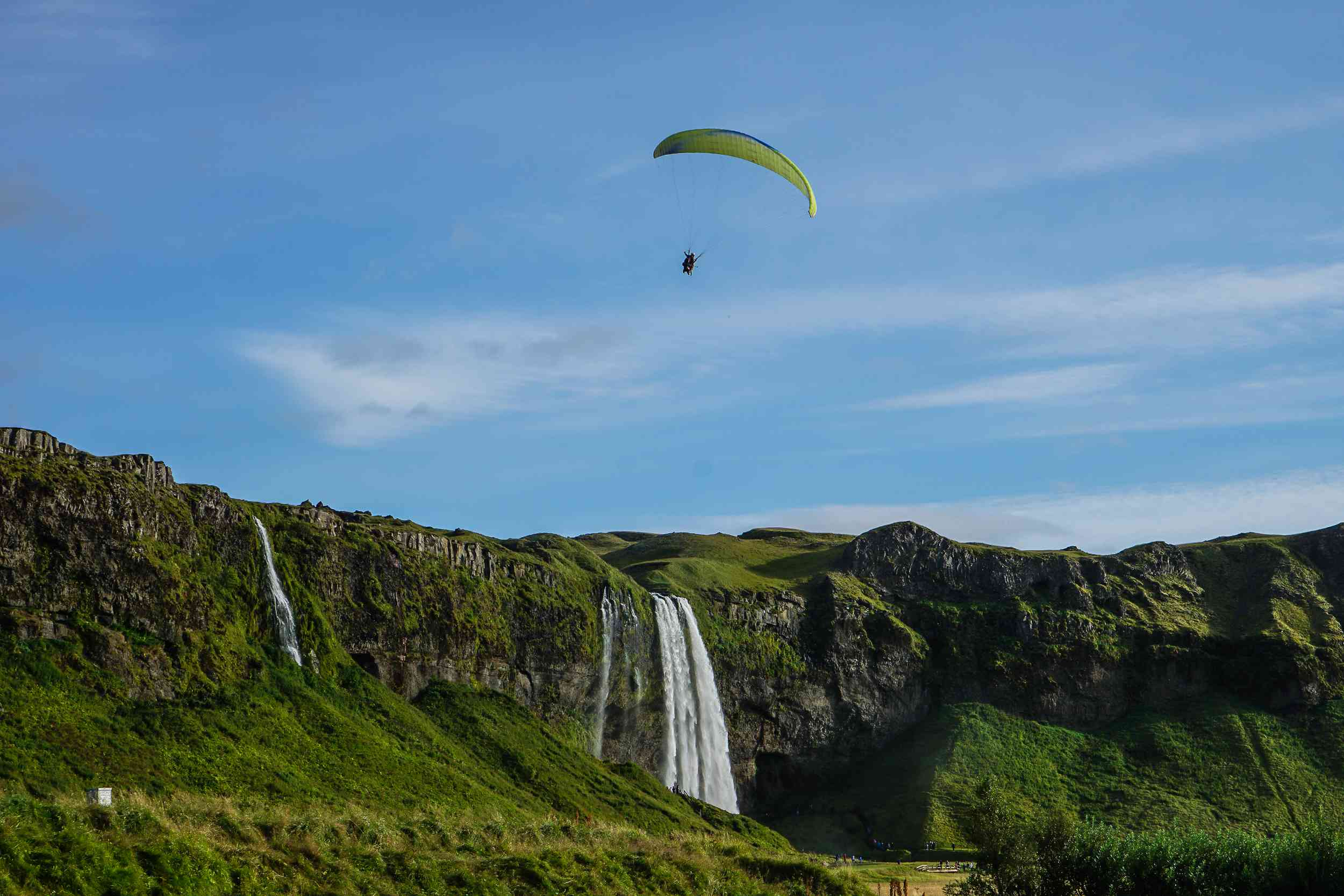 high waterfall cascading over green cliff with yellow paraglider in the sky