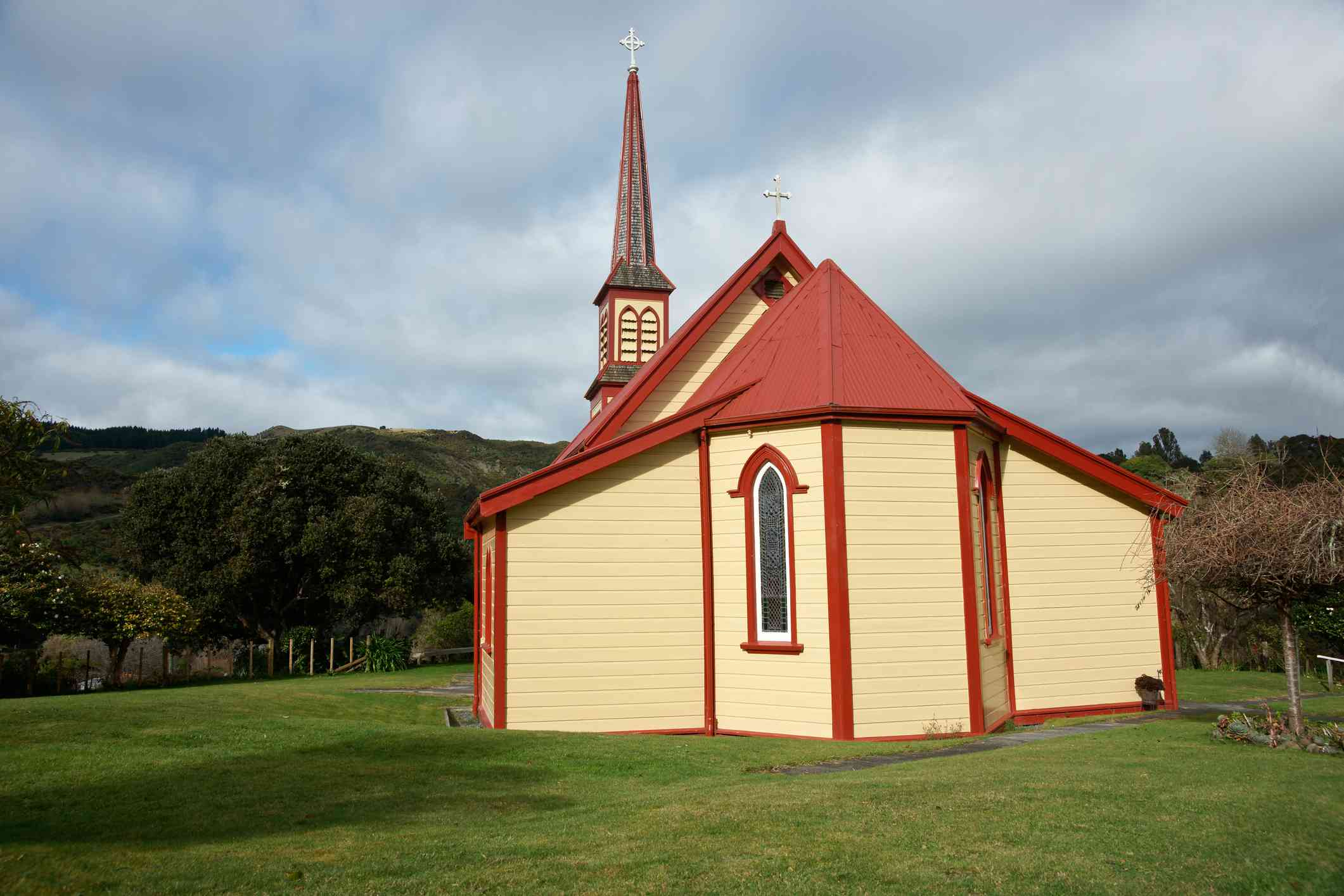 backview of a small tan and red church in a grassy field
