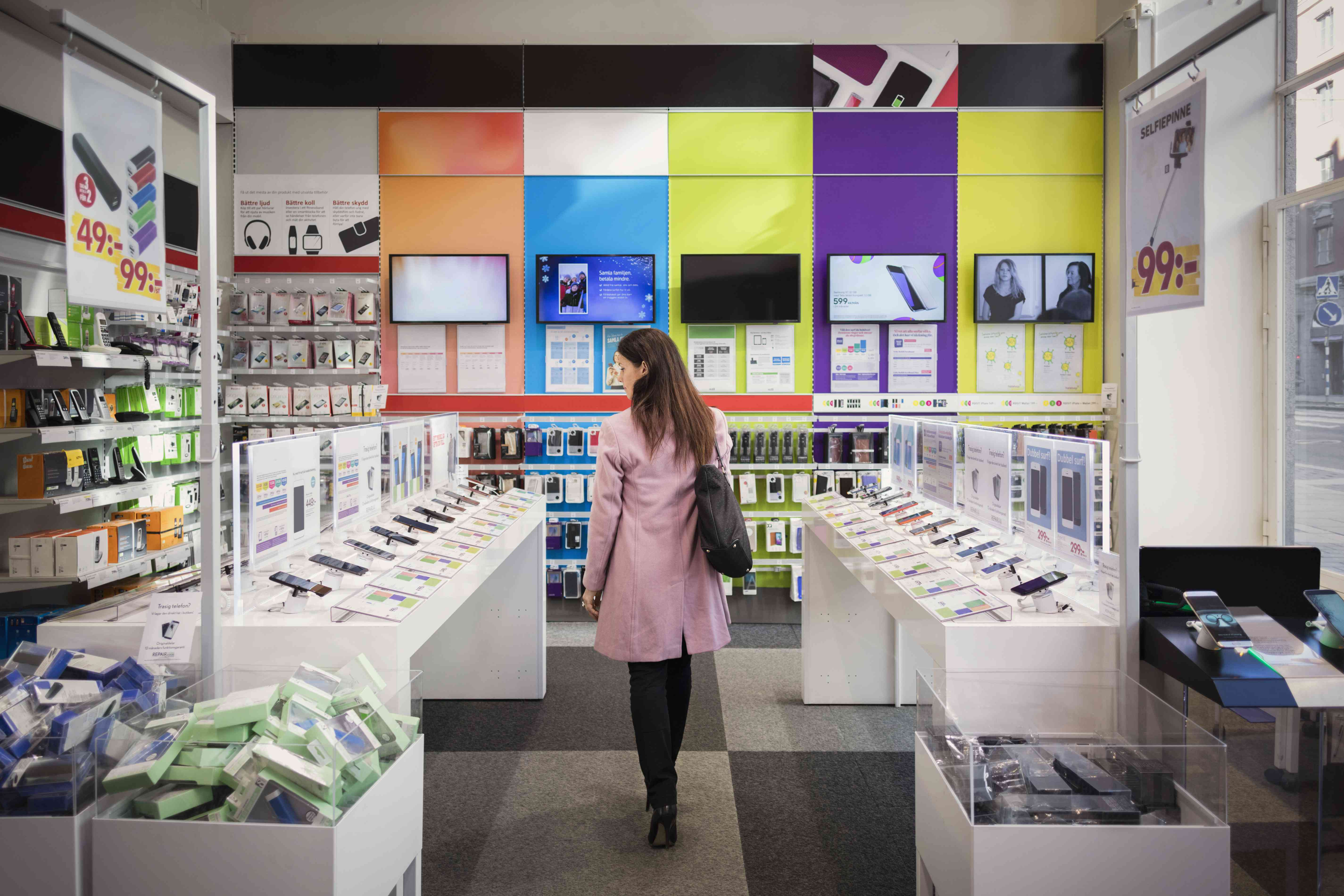 Woman browses smartphones for sale in shop