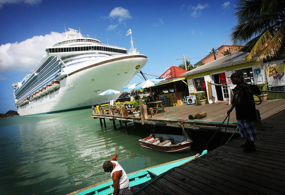 Fishermen tie up their wooden boat next to a cruise liner in St John's Harbour on March 10, 2008 in St John's, Antigua.