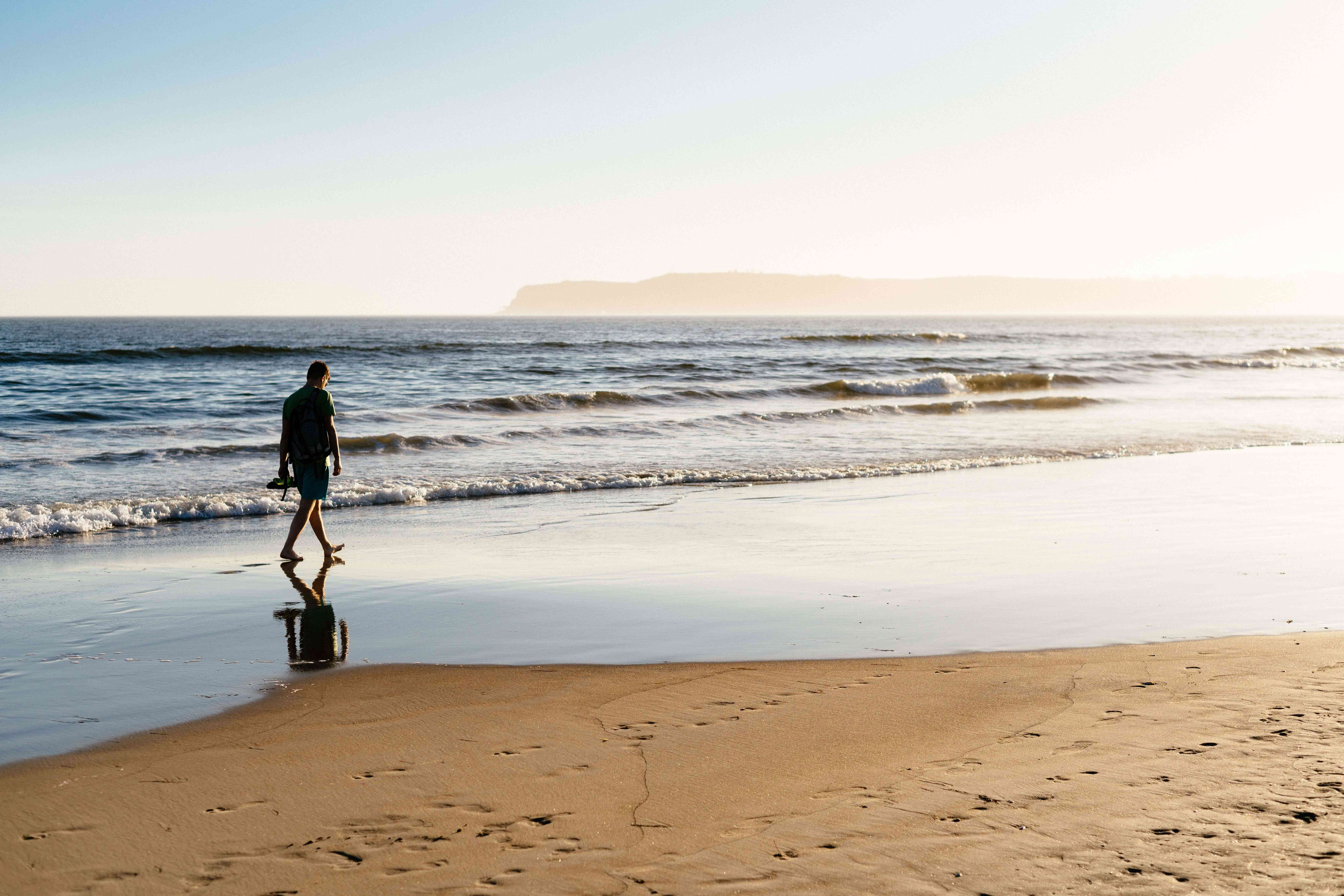 Un hombre caminando por la playa