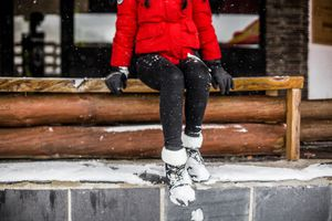 Women sitting on railing wearing winter boots