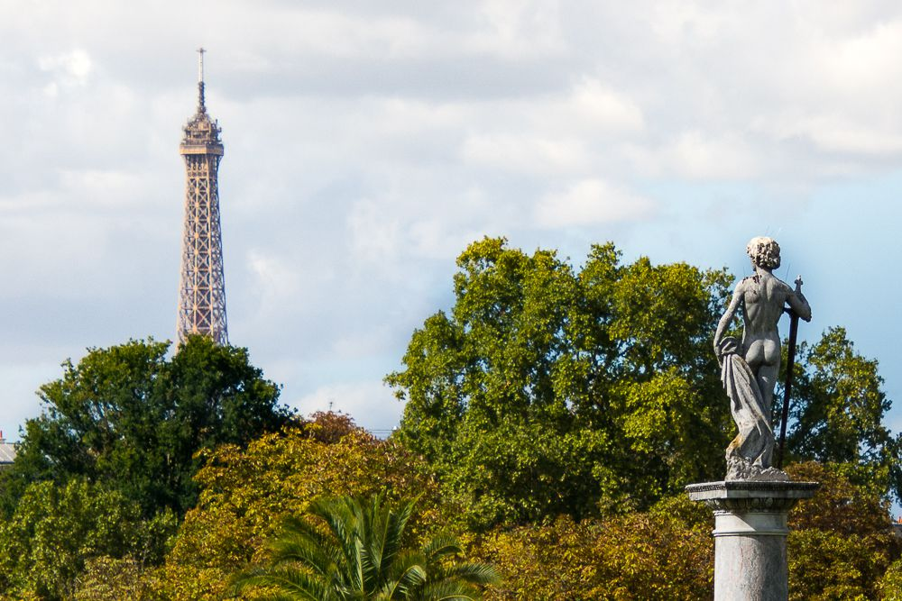 View of top of the eiffel tower and a statue