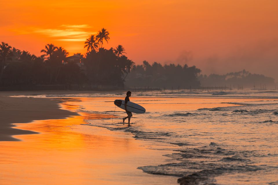 A surfer at sunset in Bali
