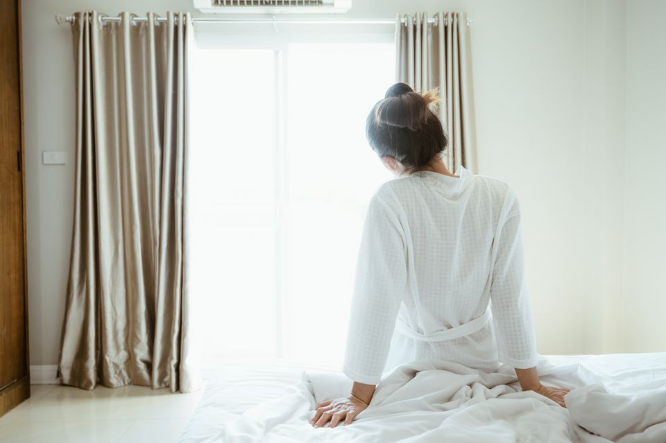 Back view of young woman looking to the view outside, sitting in bed after wake up in the morning. Start the new day with happiness.