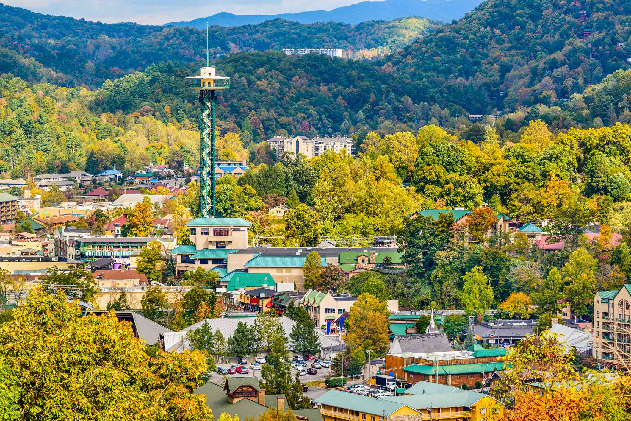 green observationtower rising out of a small town surrounded by yellow trees