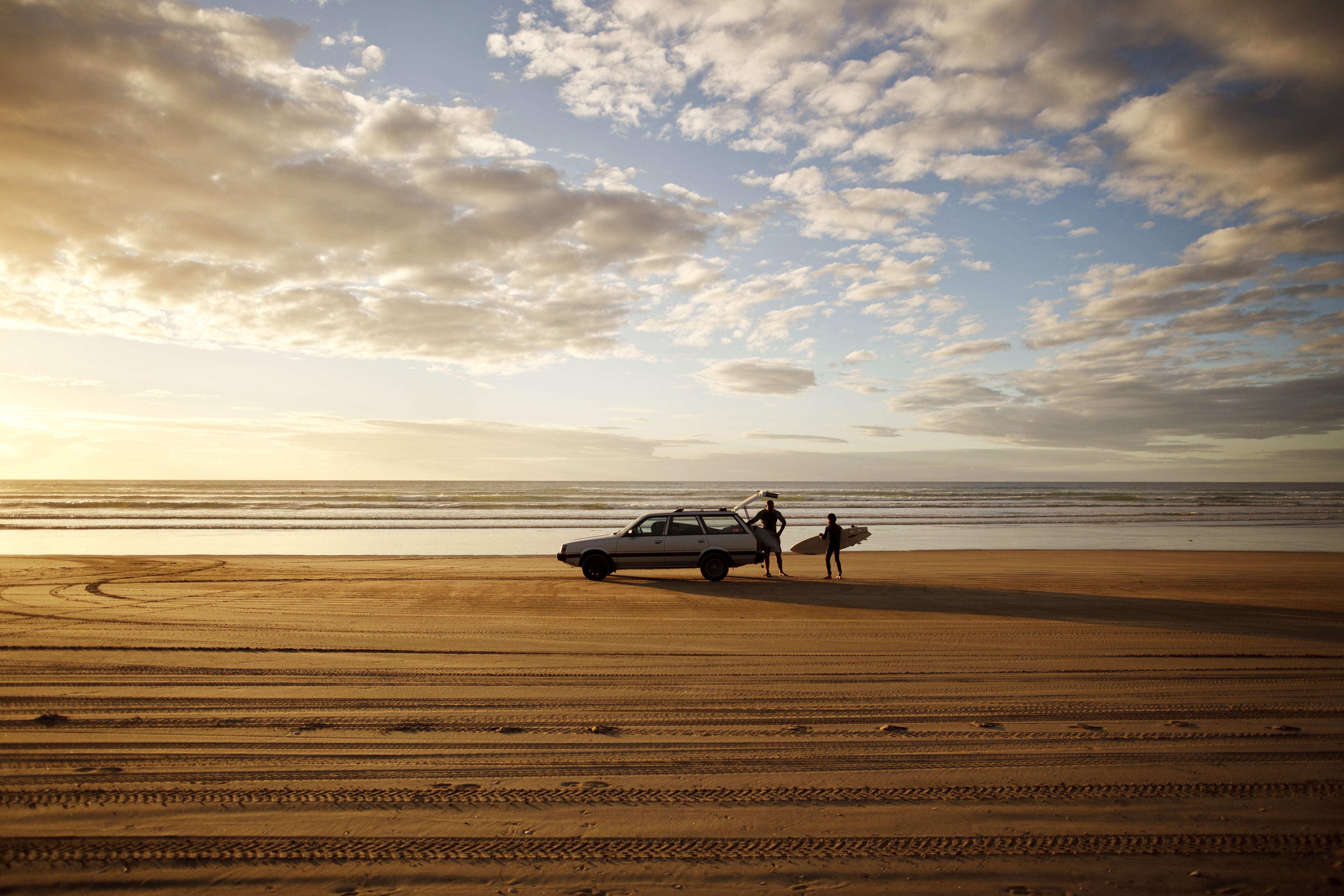 Padre e hijo cargan sus tablas de surf en su automóvil después de surfear en 90 Mile Beach