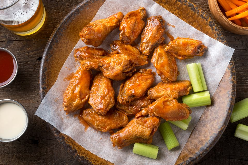 spicy Buffalo chicken wings with beer, celery, carrot sticks and dipping sauces.