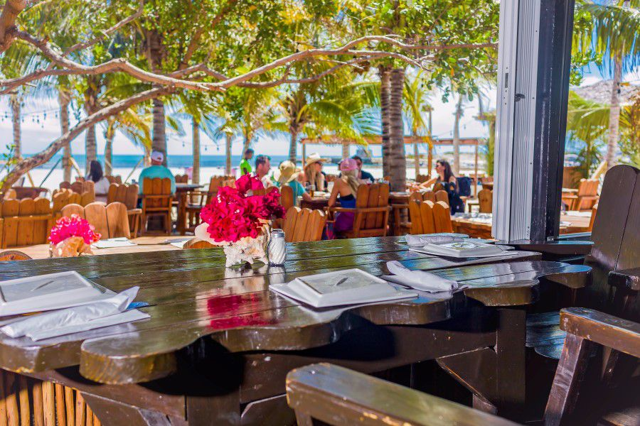 Dark wooden table with a view of outdoor beach restaurant seating