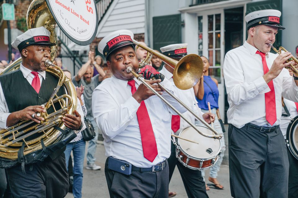 A jazz band in New Orleans walking and playing down the street