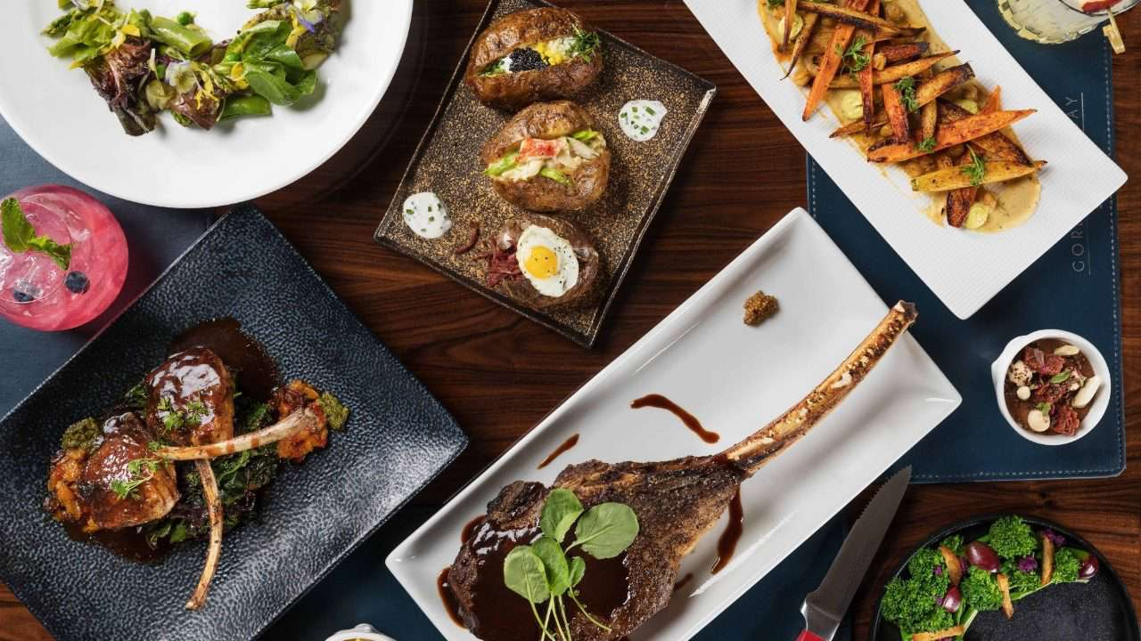 Restaurant dining table with tomahawk steak, baked potatoes, and vegetable side dishes