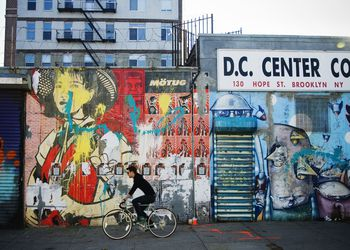 Guy riding his bike in front of a wall of graffiti in Brooklyn