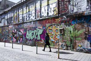 Woman walking in front of a mural in Belleville area on Denoyez street in paris