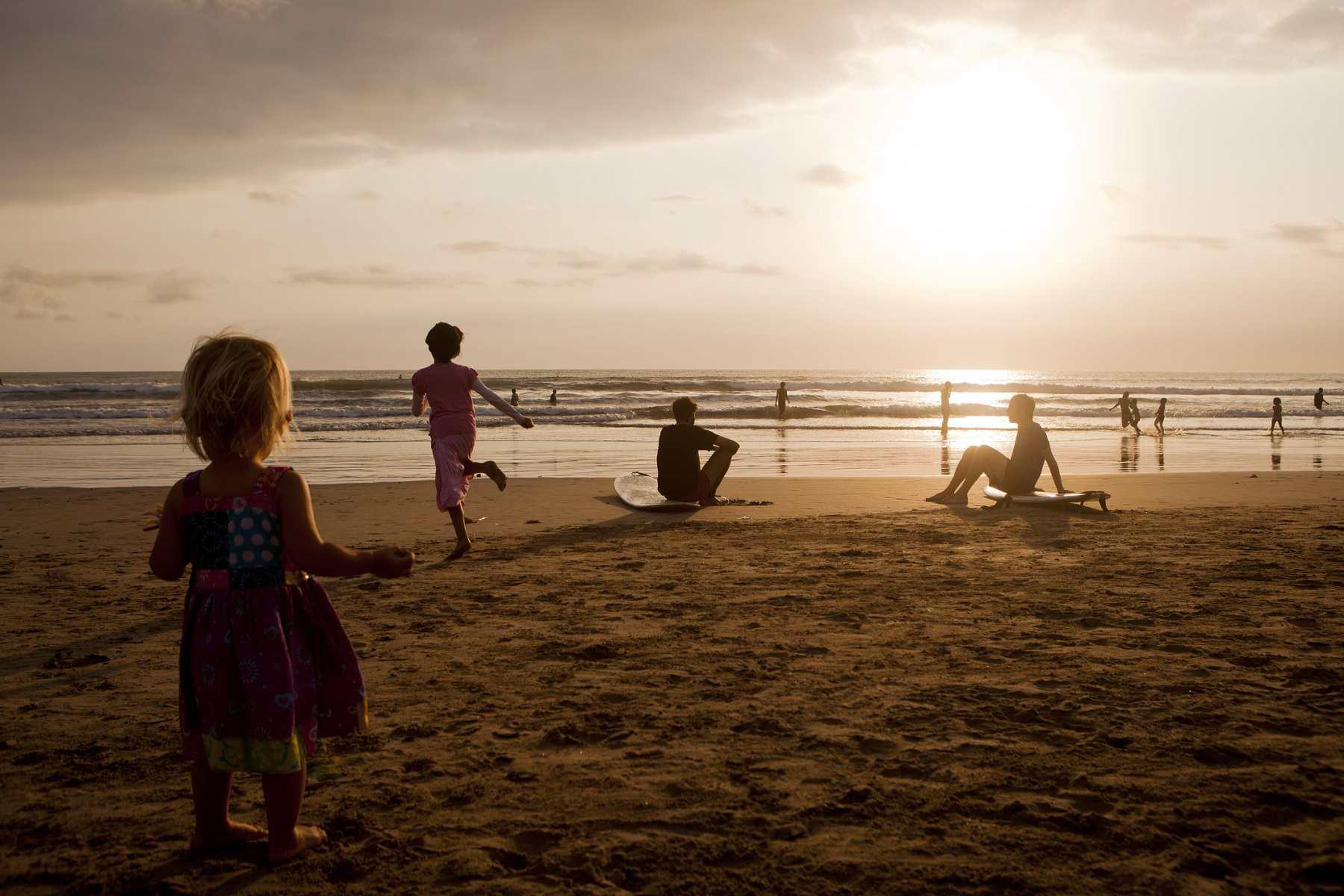 Children playing and surfers watching the sunset on Kuta Beach.