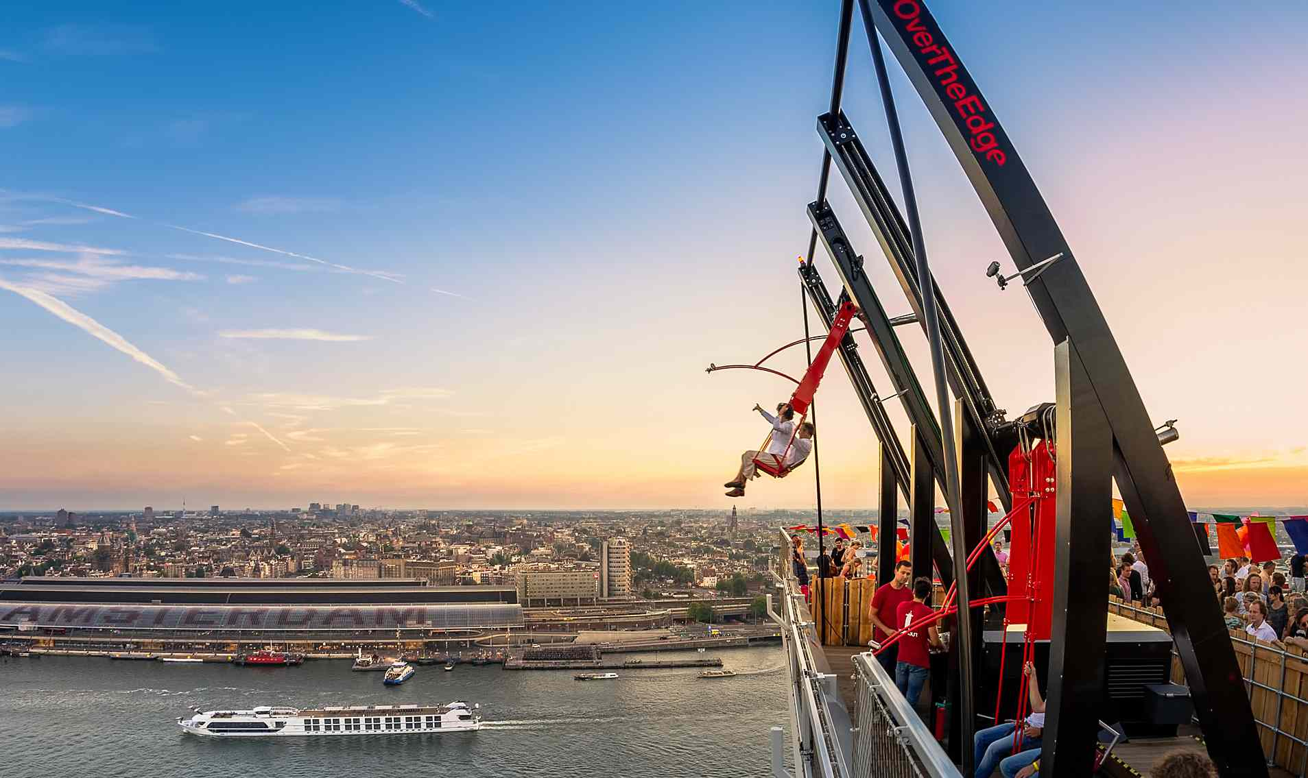 Two people on a red swing swinging from the top of A'Dam Tower in amsterdam