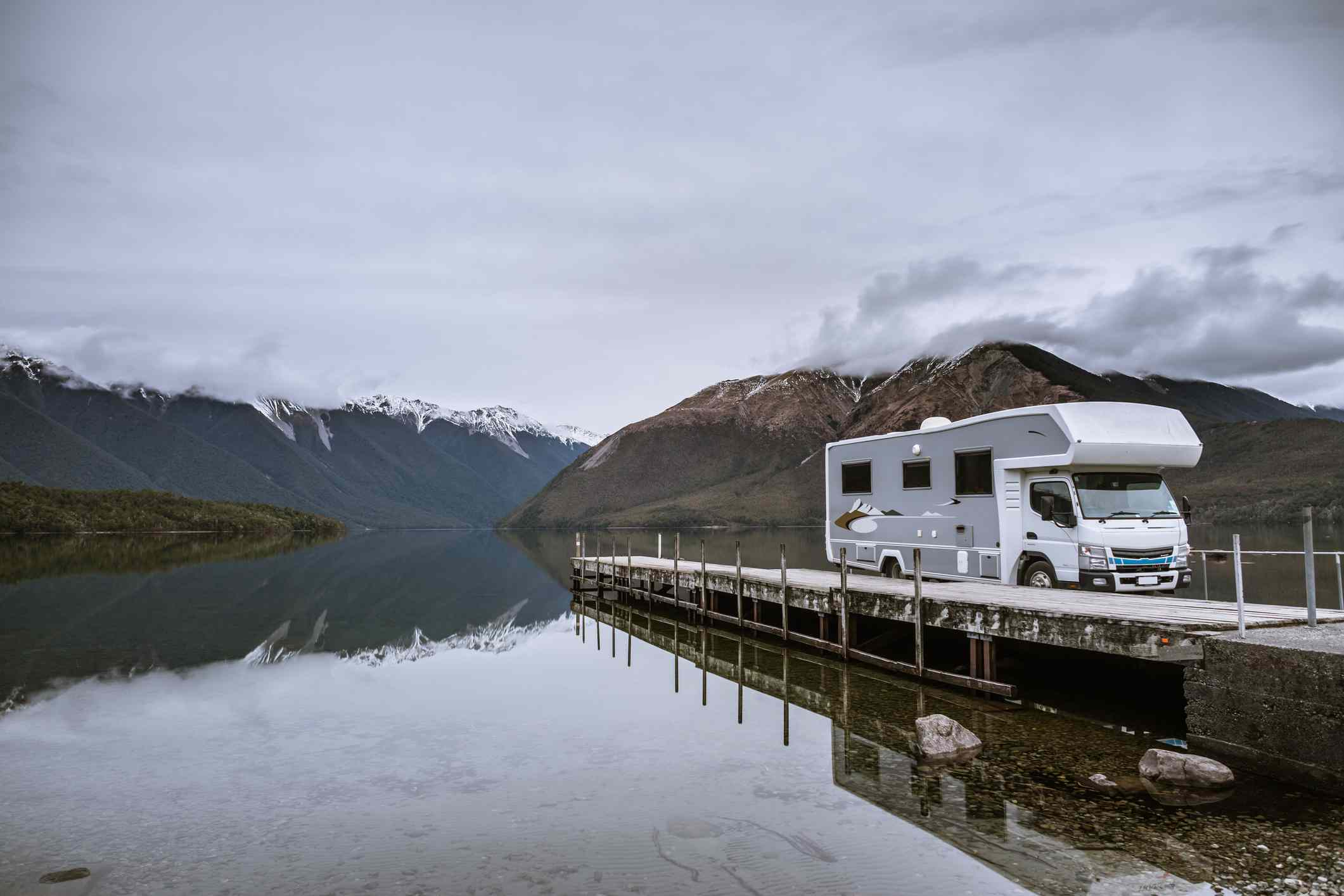 large RV parked on a jetty in a lake with snow-capped mountains in background