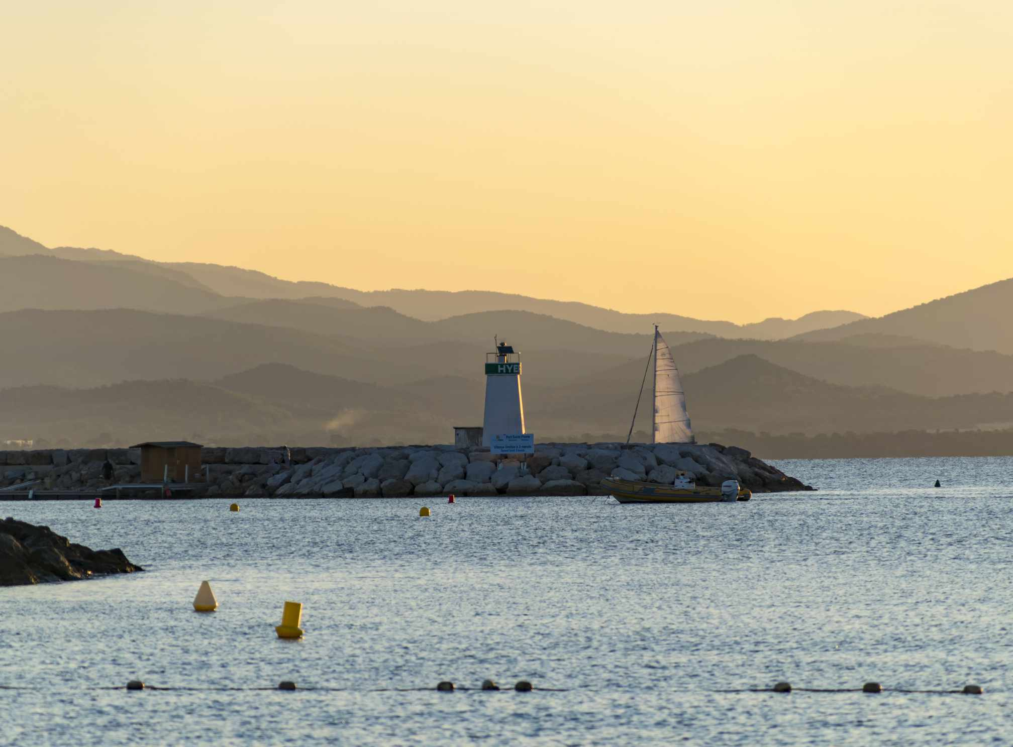 Lighthouse and sailboat at sunset, Hyères, France