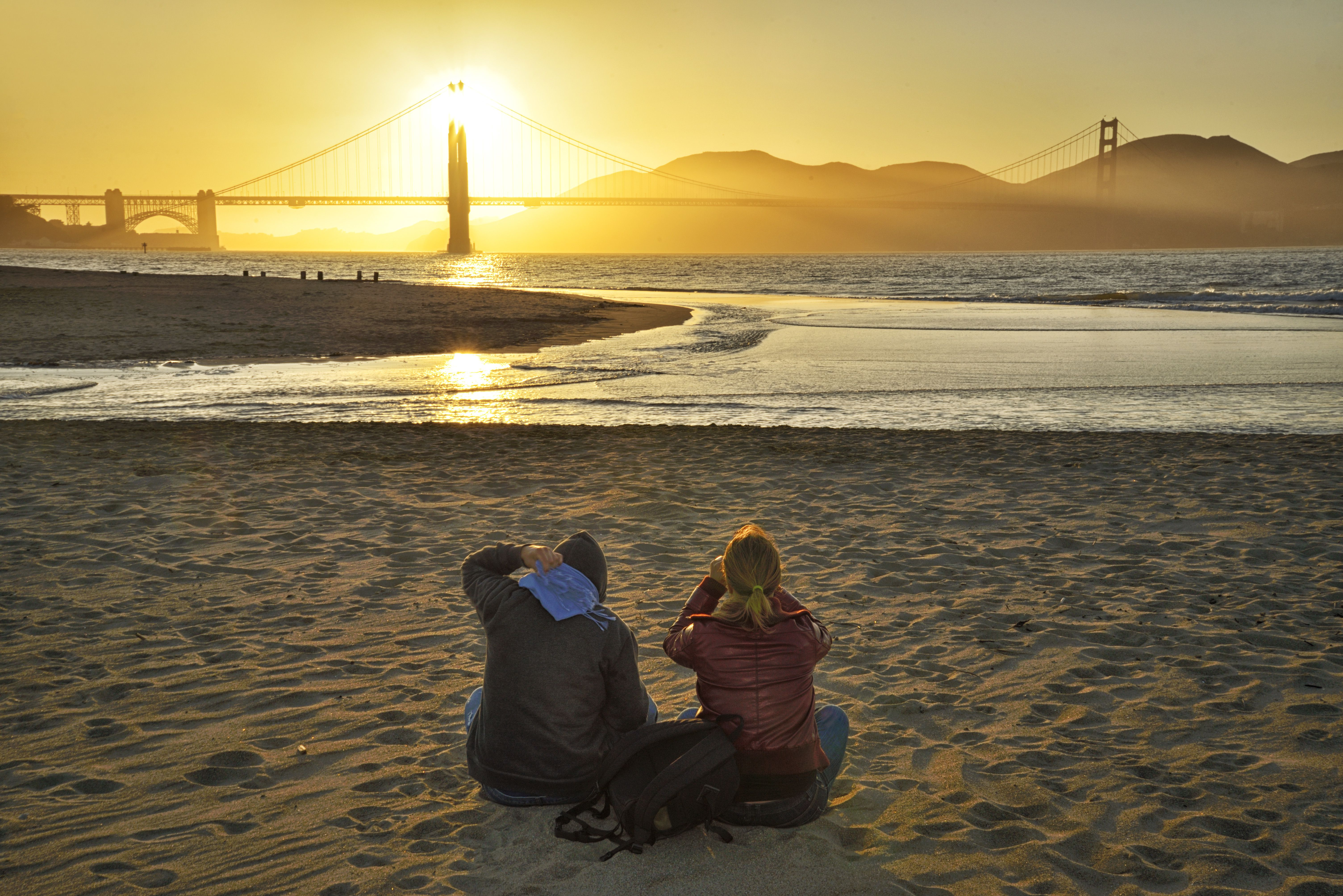 People sitting on sand at sunset beyond Golden Gate Bridge