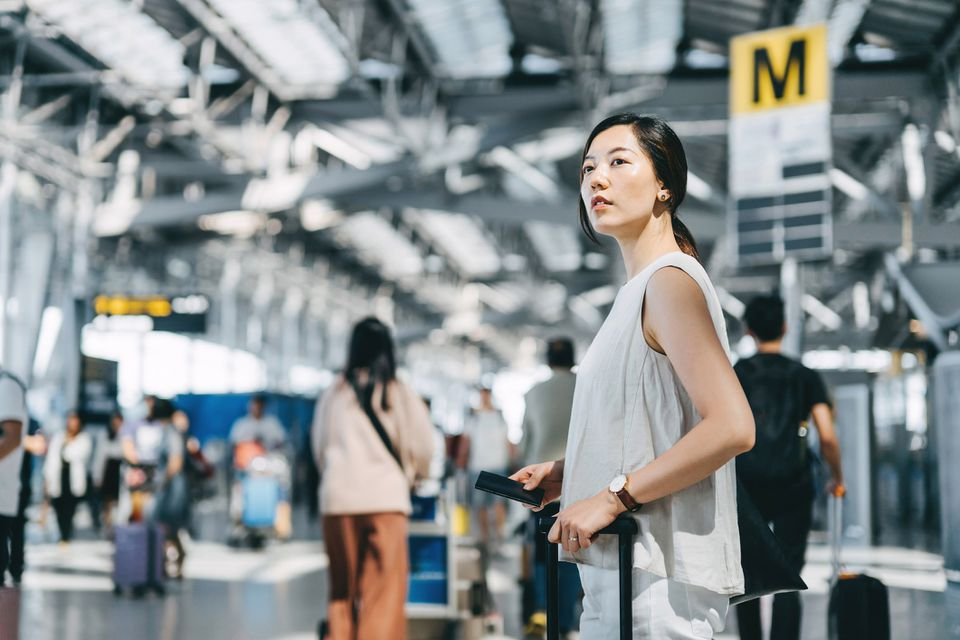 Young Asian woman traveller holding passport and suitcase walking in the international airport hall