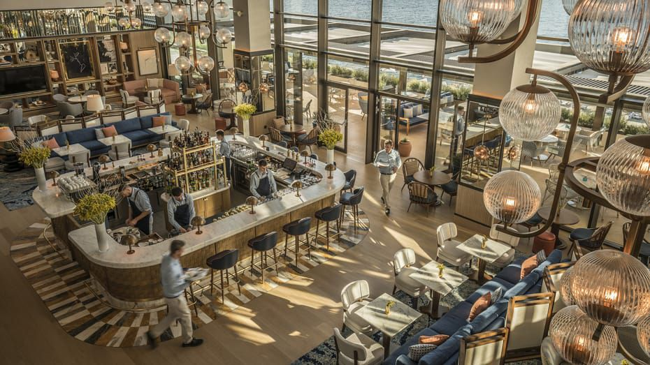 Aerial shot of Avra Bar in the Four Seasons athens. There is a 360 bar with tall chairs and floor to ceiling windows leading to an outdoor terrace
