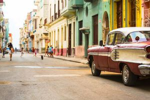 A street in Cuba with a retro car and kids playing