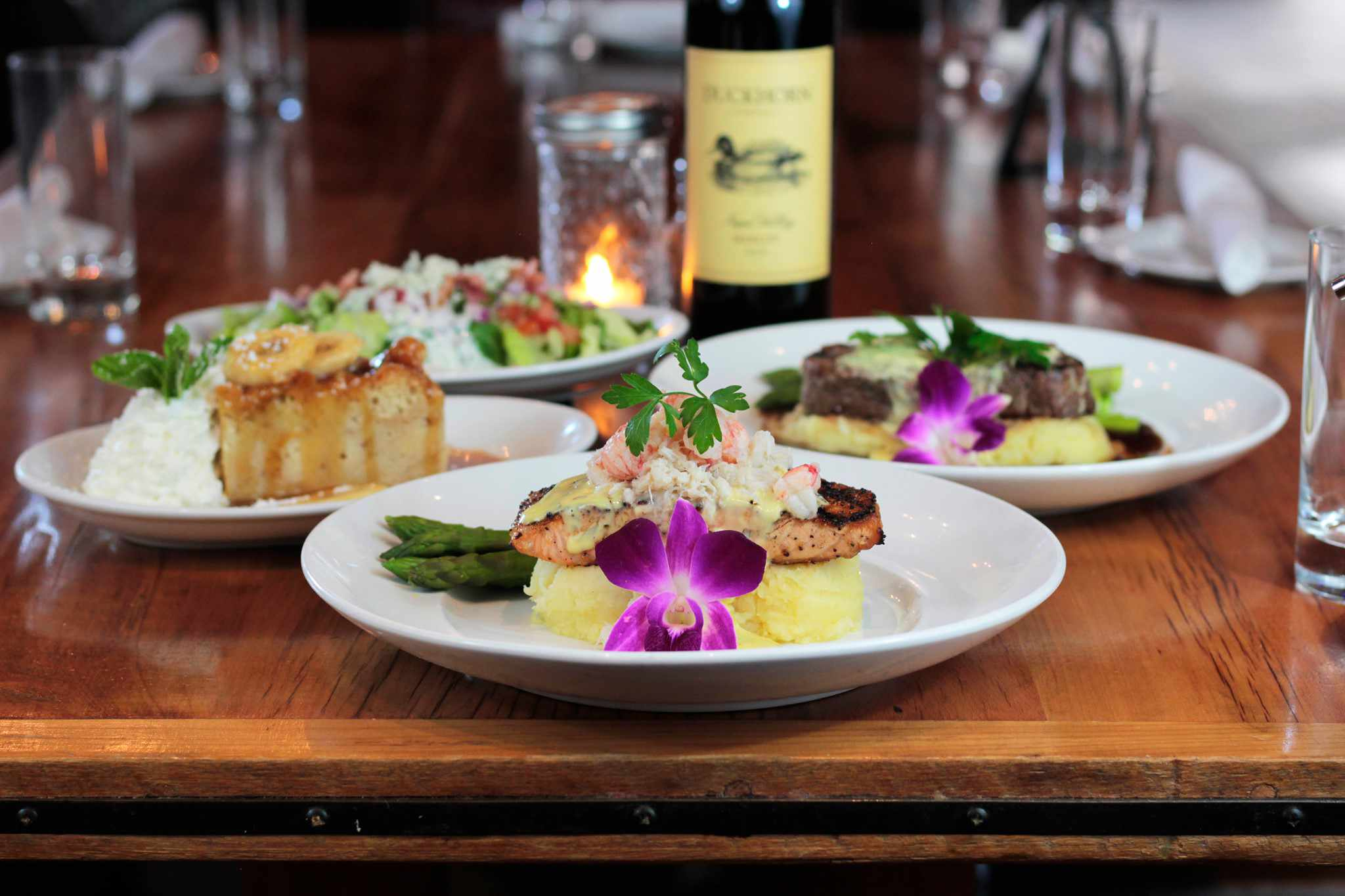 four entrees on a restaurant table with a bottle of wine. Two of the plates are garnished with a purple flower