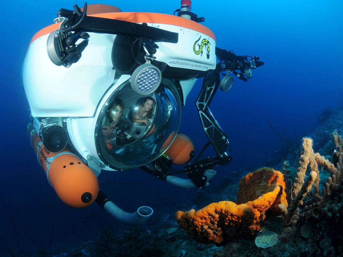 Two people underwater in Curaçao in a personal submarine encased in glass and bearing mechanical arms and lights, studying a coral reef up close.