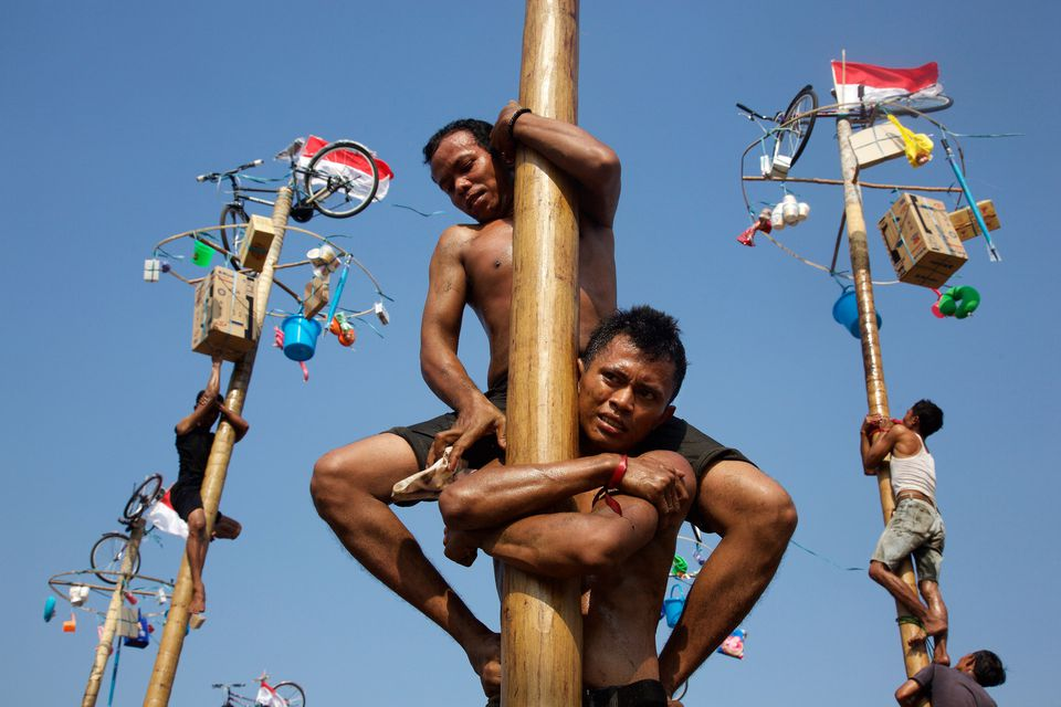 Men climb poles during panjat pinang on Indonesia Independence Day