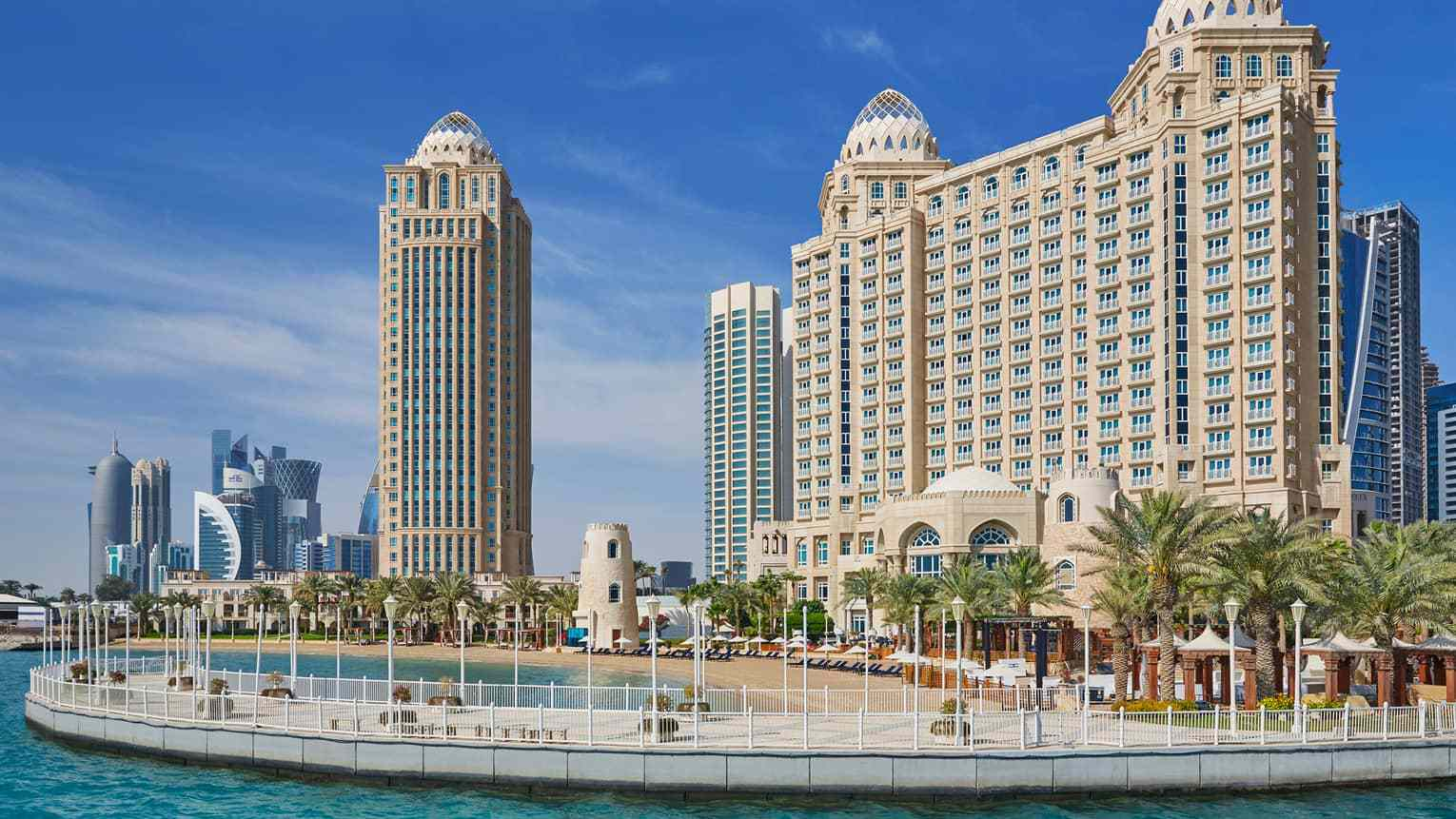 The Four Season Doha Hotel photgraphed from the water with views of the beach and shoreline palm trees