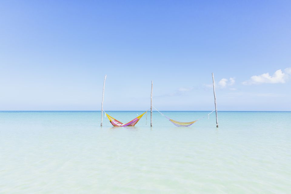 Two hammocks in the crystal clear turqoise water at a beach on the Island of Holbox, Mexico