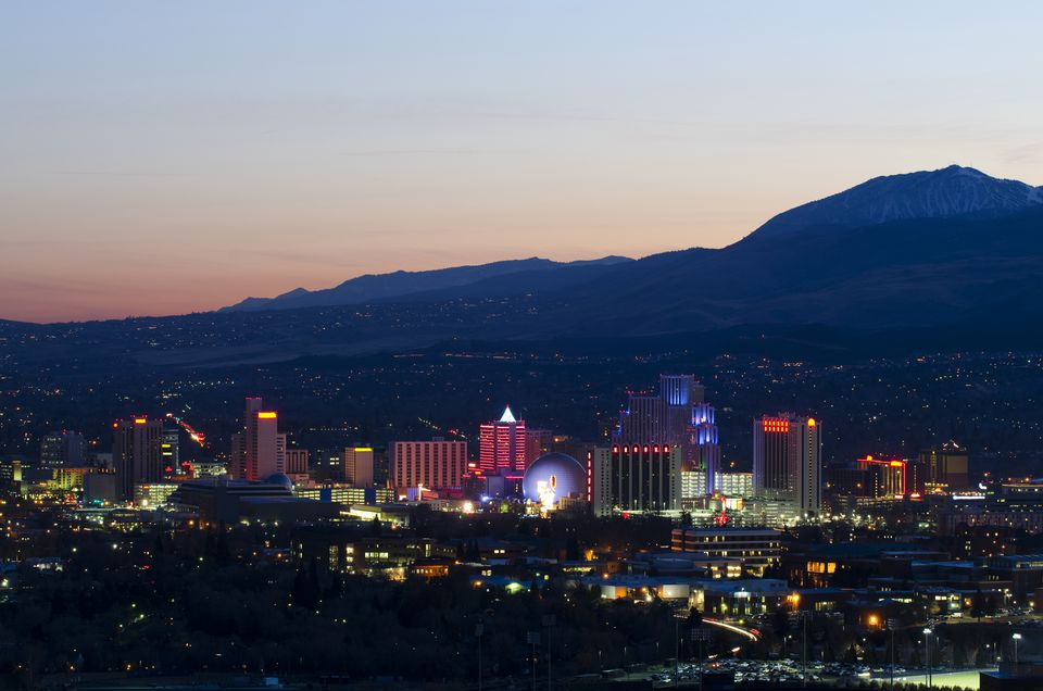 The Reno skyline is illuminated at dusk against the backdrop of the Sierra Nevada mountains, Nevada.