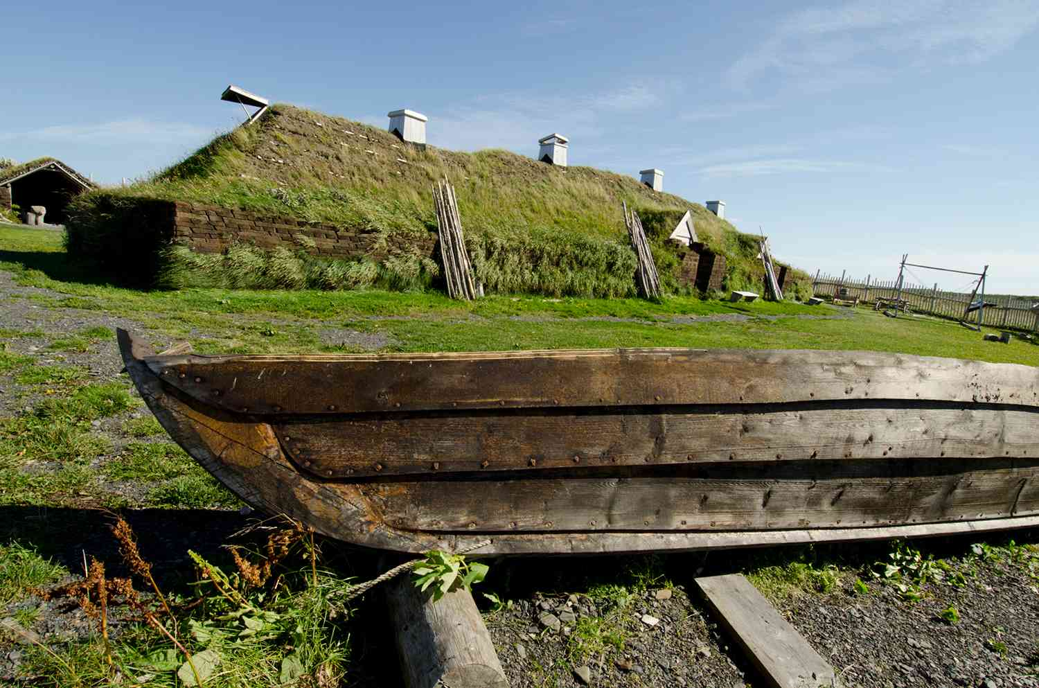 Viking style boat in front of reconstructed sod Norse long house