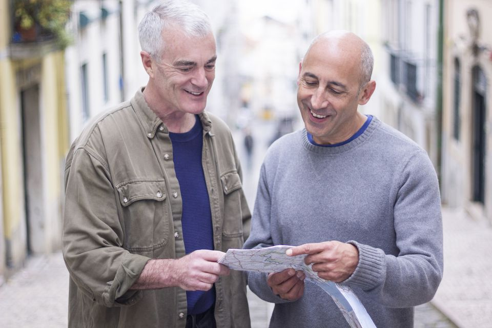 Gay senior male couple on vacation looking at map
