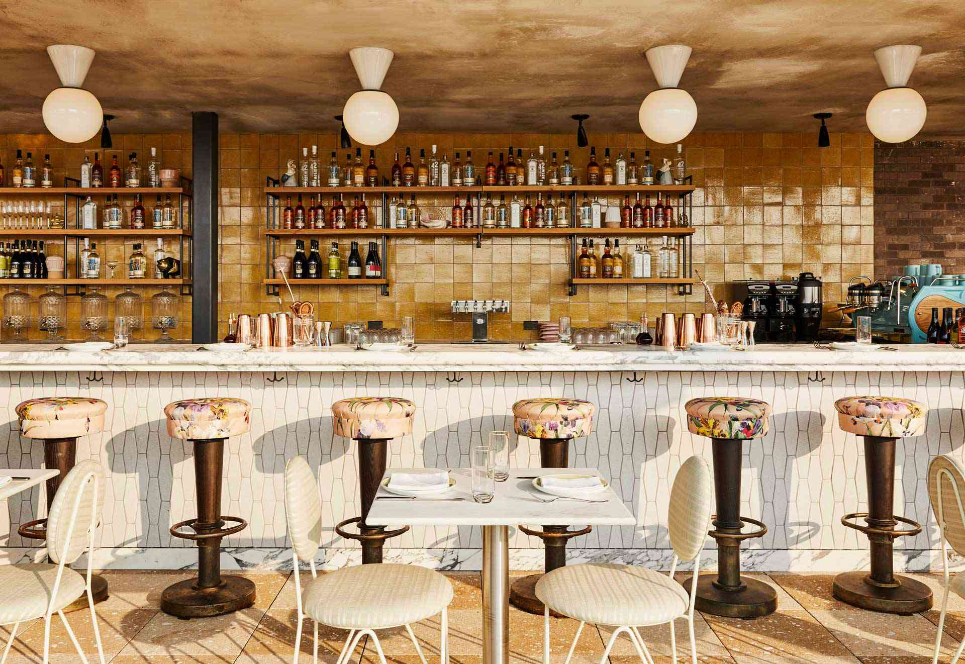 White tiled outdoor bar with stools covered in floral ulphostery