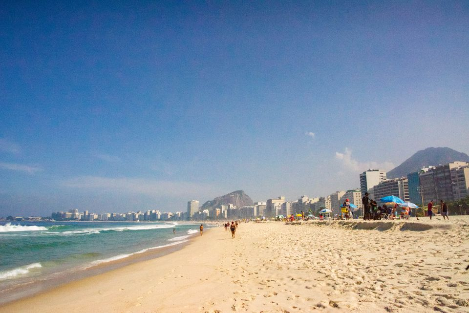 Wide shot of Copacabana beach with the skyline and the mountain in the background