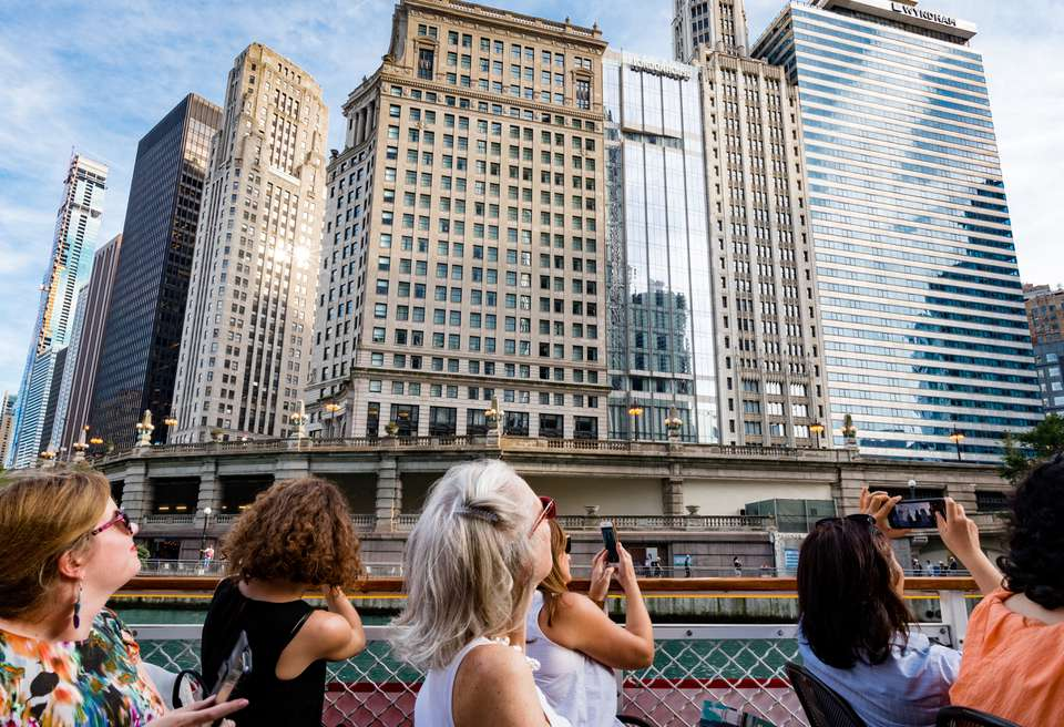 People taking photos of building on an architecture cruise