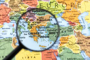Map of Greece with magnifying glass highlighting the area.