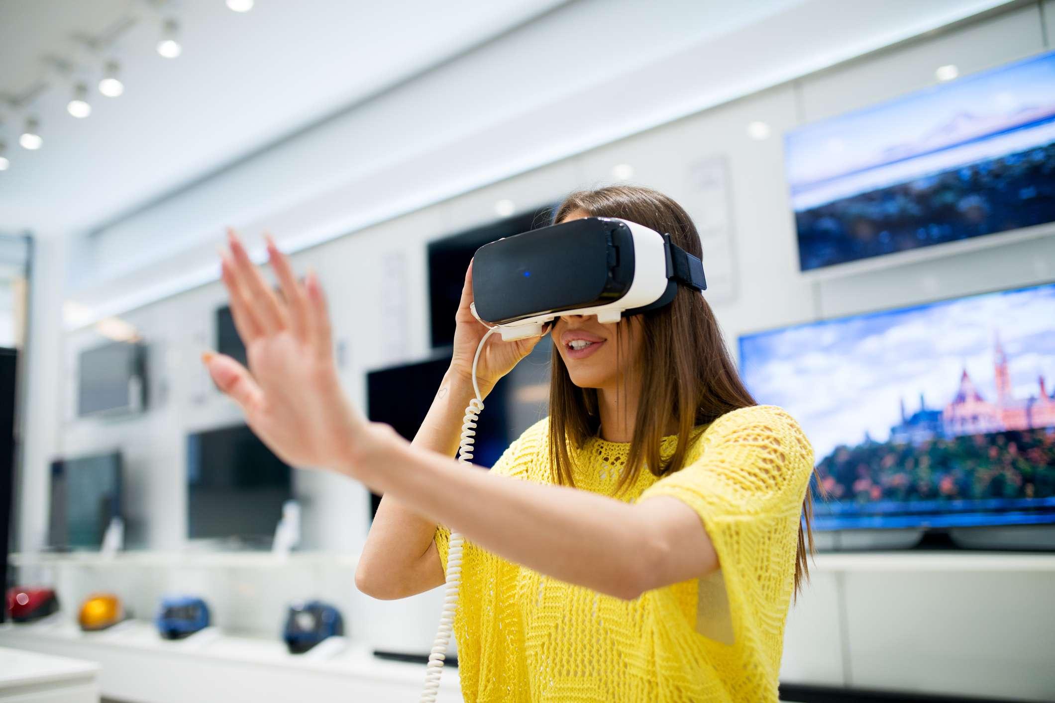 Bastante joven está probando auriculares VR en la tienda de electrónica