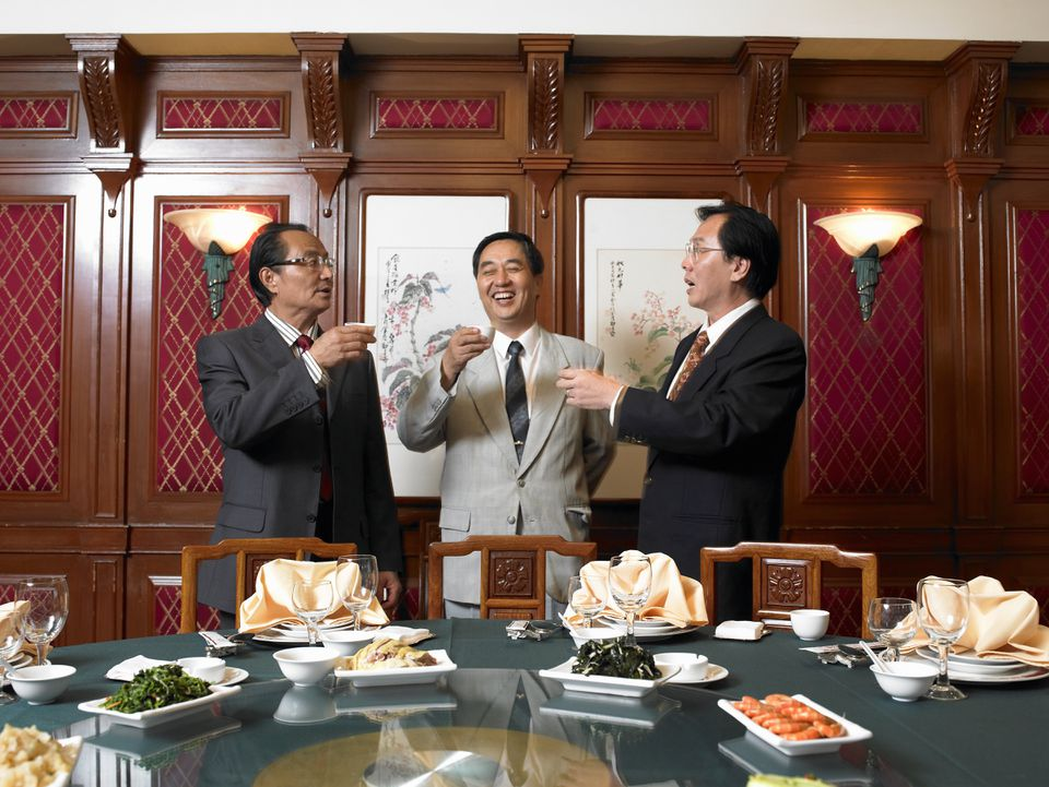 Three businessmen toasting at a banquet in China