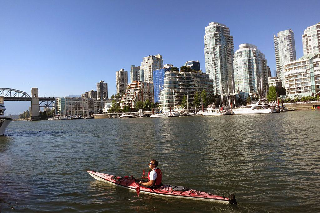 A kayaker enjoys False Creek in Vancouver on a warm sunny summer day in front of condominiums and the downtown district.