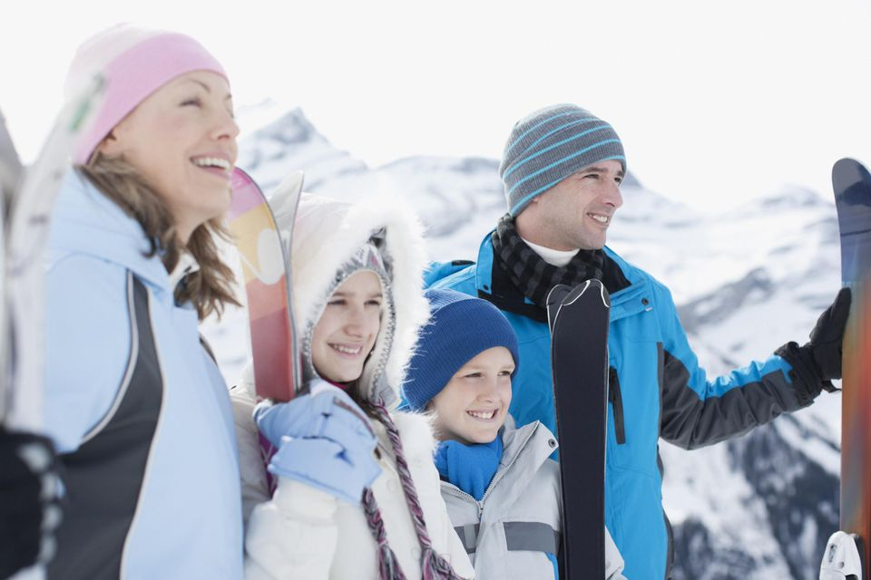 Family standing with skis