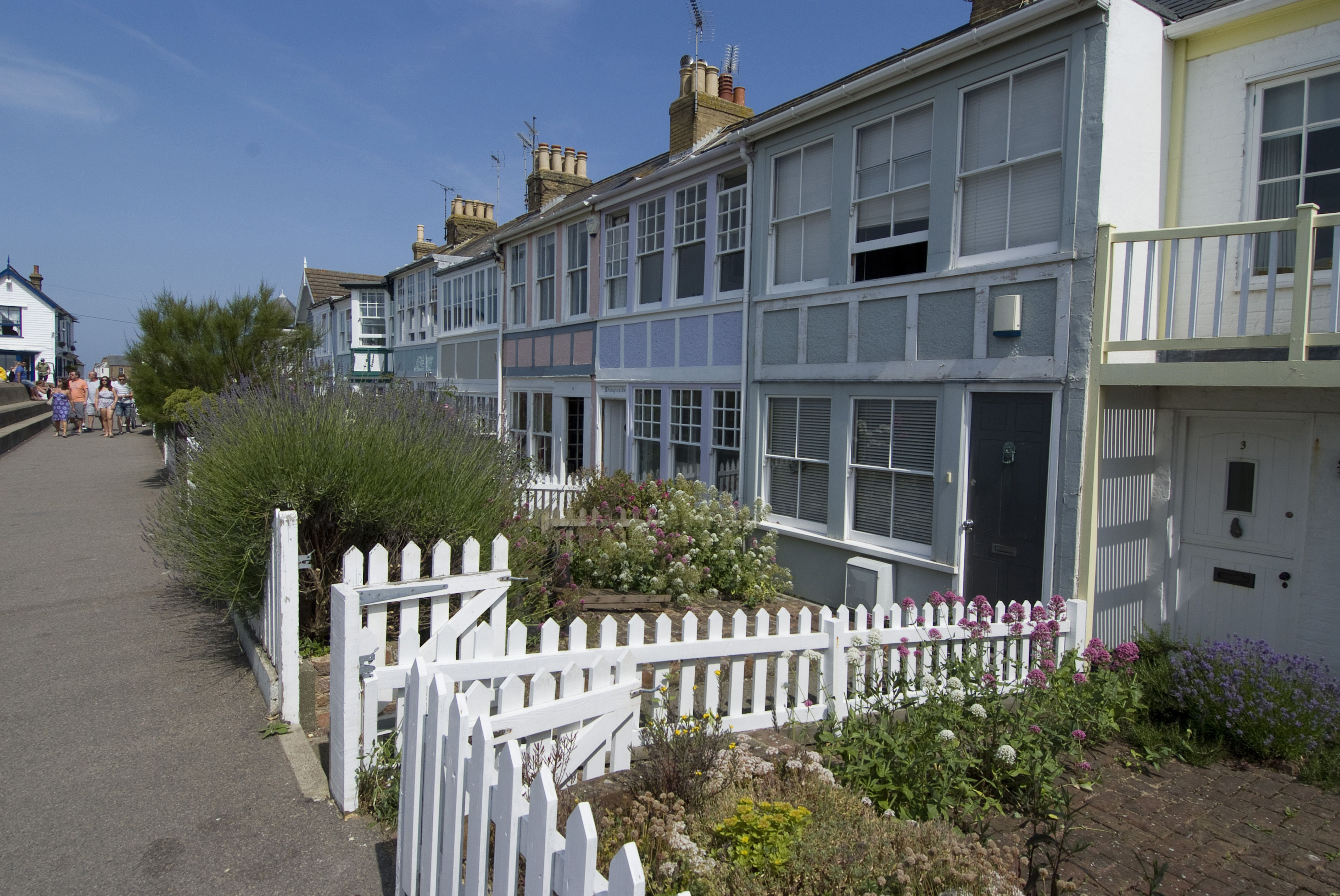 White picket fences in front of holiday waterside houses, Whitstable, Kent, England